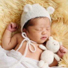 Newborn baby girl wearing crochet bear ears holding teddy bear sleeping on sherpa rug in studio