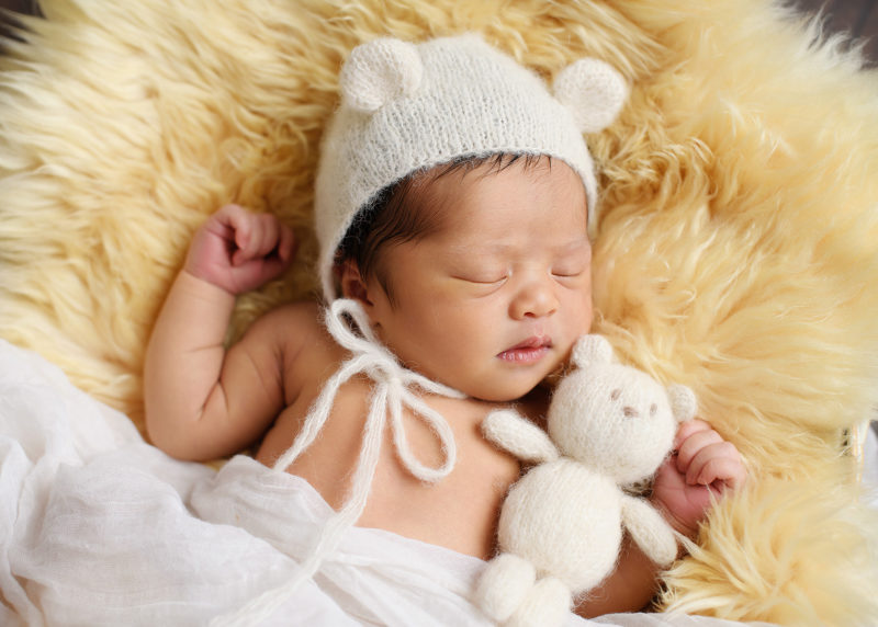 Newborn baby girl wearing crochet bear ears holding teddy bear sleeping on sherpa rug in studio