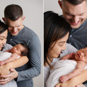 Mom and dad smiling while looking at sleeping newborn baby girl in Sacramento studio