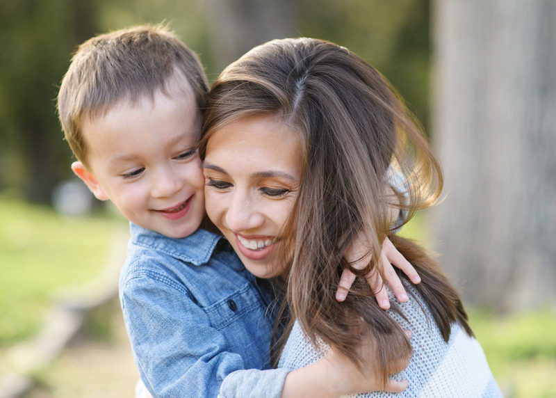 Mom and son smiling and hugging outdoors in Land Park Sacramento