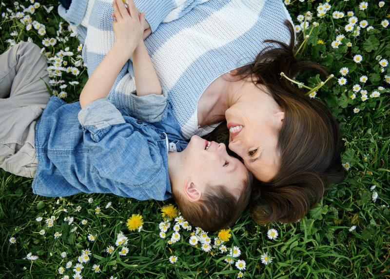 Mom and son lying on grass and smiling at each other aerial view next to wildflowers