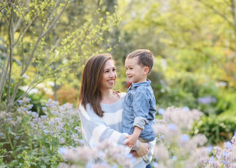 Mom holding son and smiling in the middle of wildflowers in Land Park Sacramento