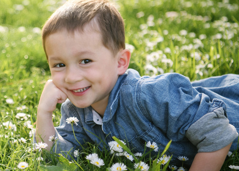 Little boy smiling with arm propping up his head and lying on grass and wildflowers in Land Park Sacramento