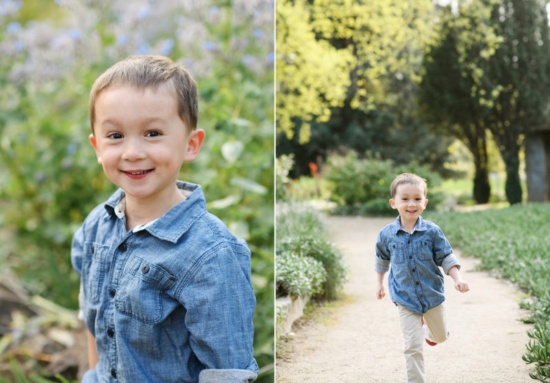 Little boy wearing denim shirt smiling directly at camera and running with trees in background in Land Park Sacramento