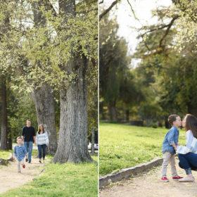 Little boy walking in front of parents outdoors near tall oak trees in Sacramento