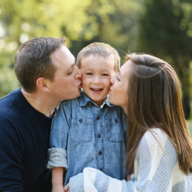 Dad and mom kissing son on cheek outdoors in Sacramento park
