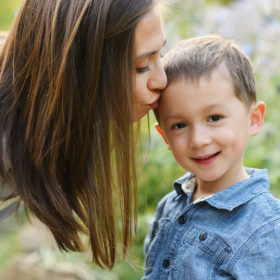 Mom kissing son's forehead as he smiles with flowers in background in Sacramento park