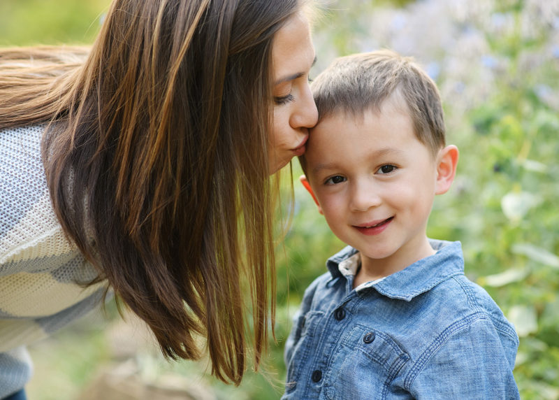 Mom kissing son's forehead as he smiles with flowers in background in Sacramento Land Park
