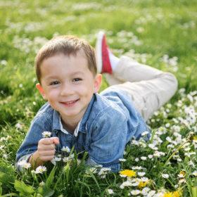 Little boy wearing denim shirt lying in grass among wildflowers in Sacramento