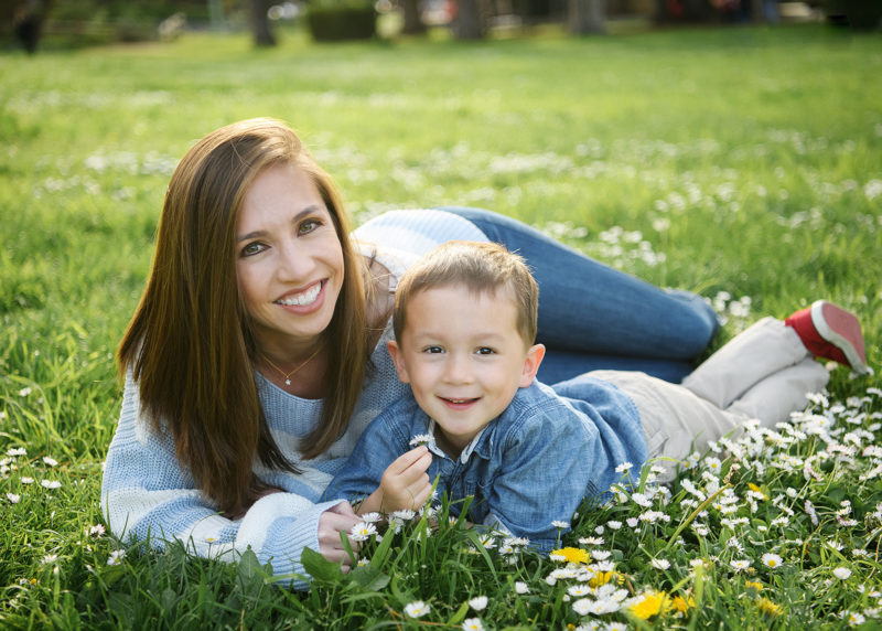 Mom and son lying in grass and wildflowers in Sacramento Land Park