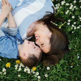 Mom and son lying on grass with wildflowers in William Land Park Sacramento