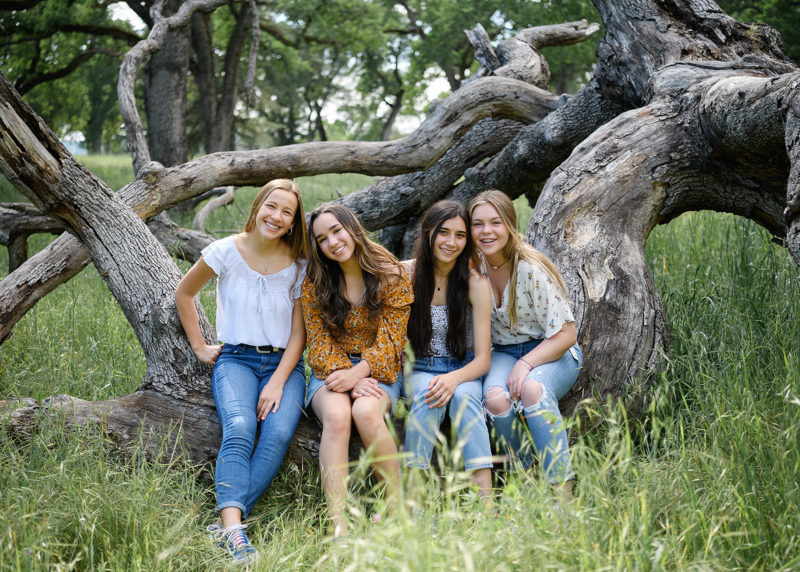 Girl friends smiling and sitting on fallen tree trunk in Folsom