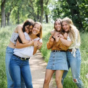 Friends hugging and smiling outdoors in park among green grass