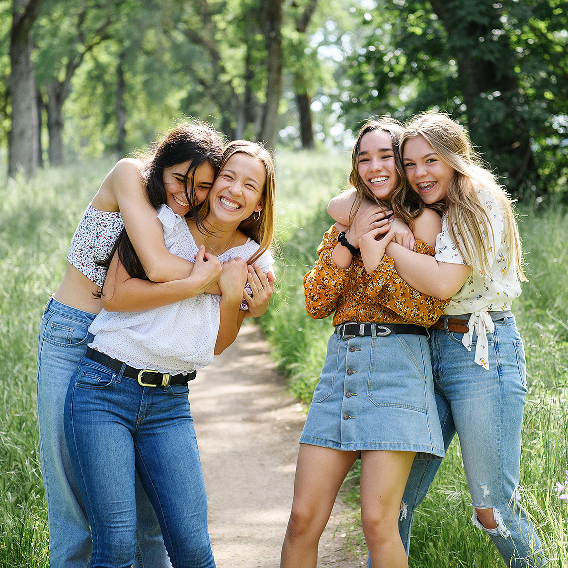 Friends hugging and smiling outdoors in park among green grass in Folsom