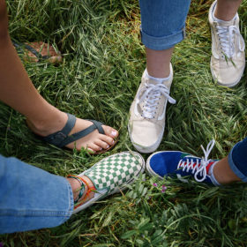 Aerial view of friend's shoes on grass including flip flops and Vans