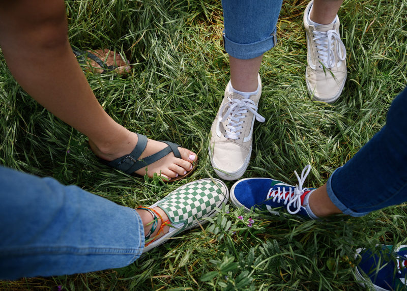 Aerial view of friend's shoes on grass including flip flops and Vans in Folsom
