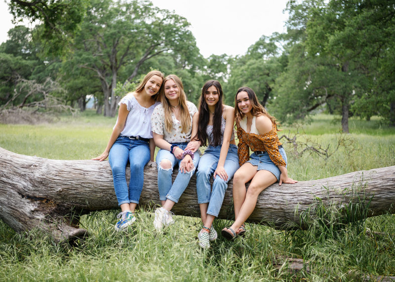 Girl friends smiling and sitting on fallen tree trunk in Folsom park
