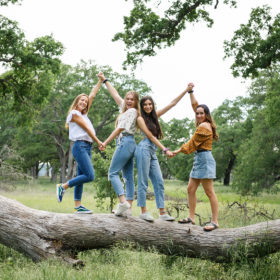 Girl friends holding hands and standing on fallen tree trunk in park