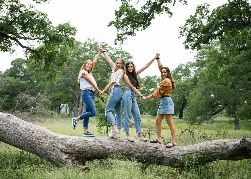 Girl friends holding hands and standing on fallen tree trunk in Folsom park