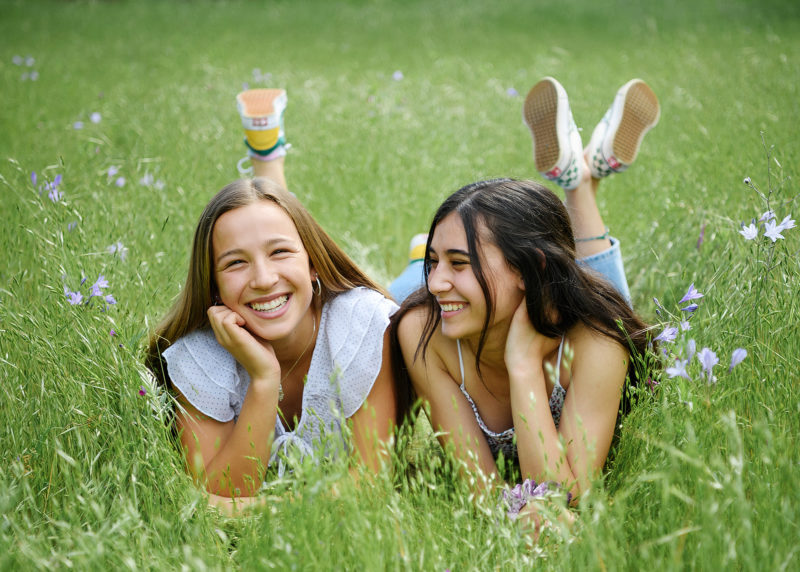 Best girl friends lying on the grass and smiling in park