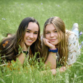 Best girl friends with hands on face smiling and lying on the grass in park