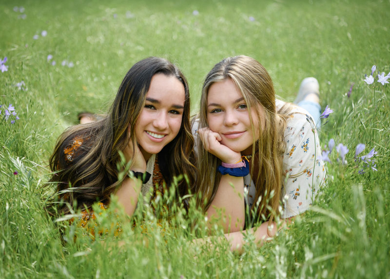 Best girl friends with hands on face smiling and lying on the grass in Folsom park