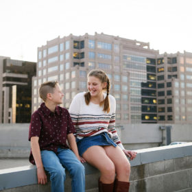 Brother and sister sitting on Sacramento rooftop overlooking cityscape
