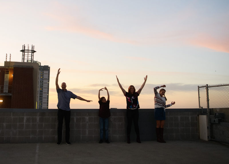 Family silhouette spelling out LOVE on Sacramento rooftop against sunset