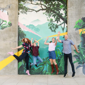 Family jumping and smiling in front of Kinetik Ideas R Street mural
