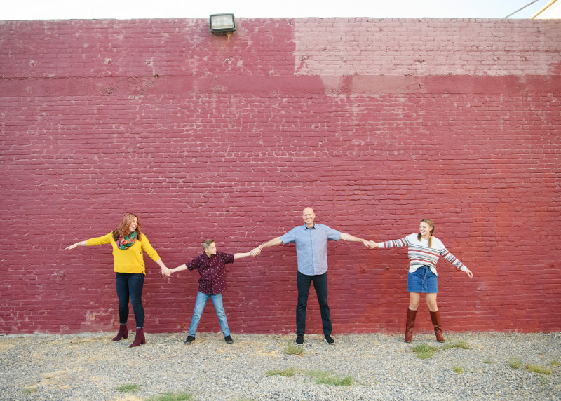 Family holding hands in front of red painted brick wall in midtown Sacramento