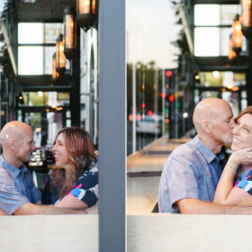 Mom and dad kissing and looking at each other lovingly in cafe through window in Sacramento