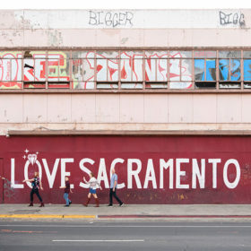 Family walking in front of LOVE SACRAMENTO mural in downtown Sacramento