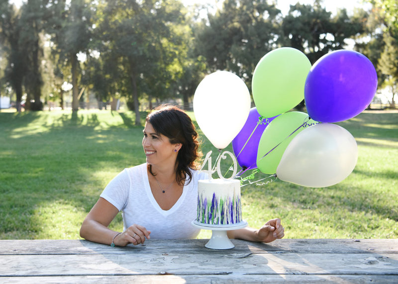 Mom smiling with balloons and cake to celebrate her 40th birthday in Sacramento
