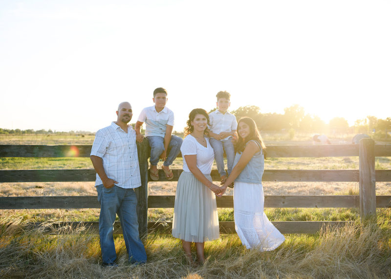 Family photo by the fence during sunset in Sacramento