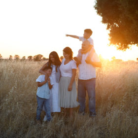 Family hugging each other on dry grass as sun sets in Sacramento