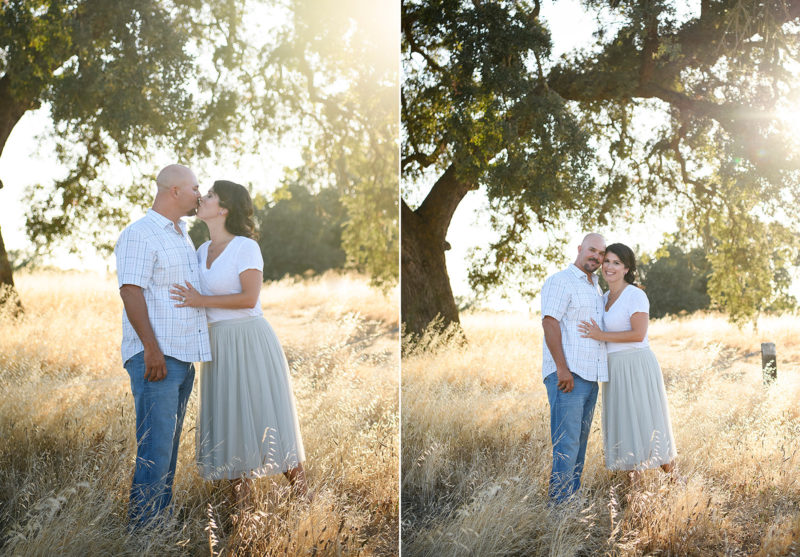 Mom and dad kissing and hugging underneath a large tree in yellow grass in Sacramento