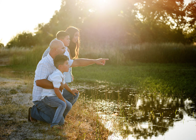 Dad and children pointing at the lake during sunset in Sacramento