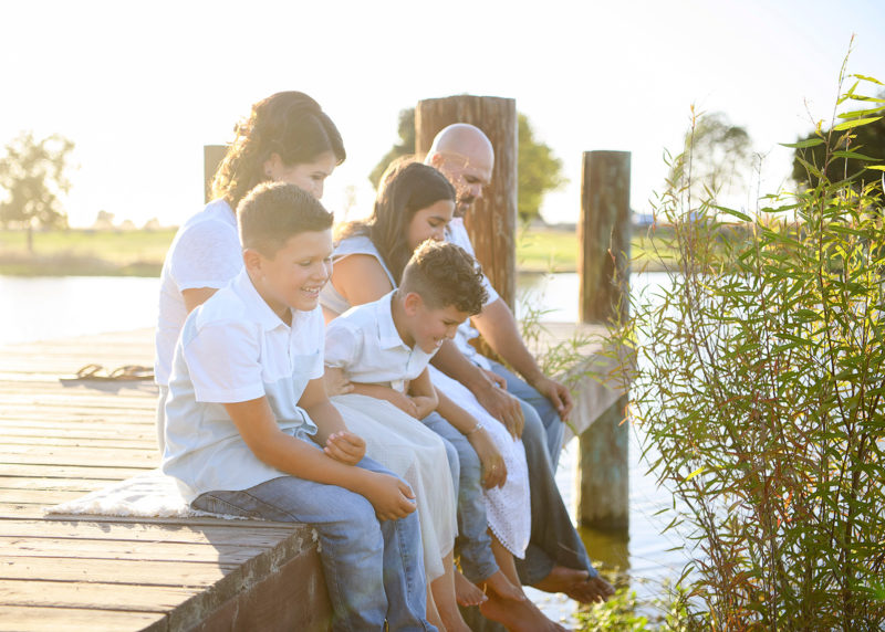 Family sitting on the dock and dipping their feet into the lake in Sacramento