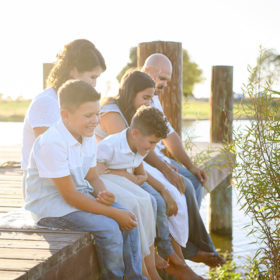 Family sitting on the dock dipping their feet in the water in Sacramento