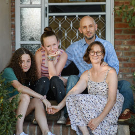 Mom, dad and daughters sitting on front porch in Sacramento