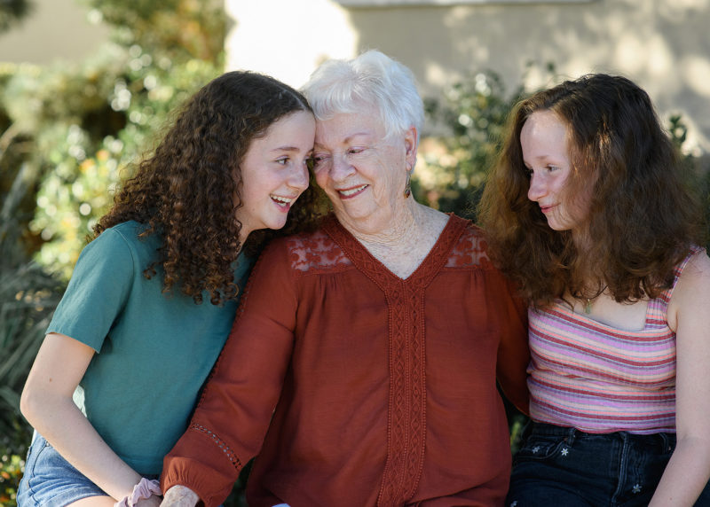 Grandma smiling and leaning into granddaughters in front of Sacramento home