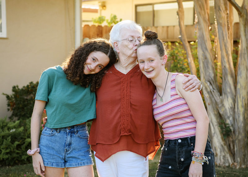 Grandma kissing her granddaughters as they reunite in Sacramento