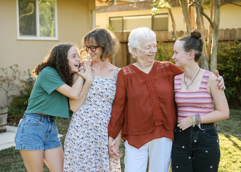 Grandma, mom and daughters look lovingly at each other in front of Sacramento home