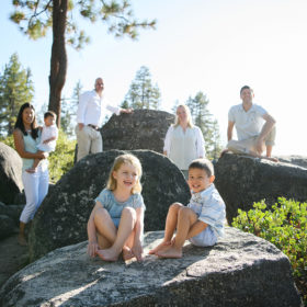 Boy and girl sitting on large rock with parents in background at Lake Tahoe