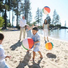Families tossing around beach balls in the sand at Lake Tahoe