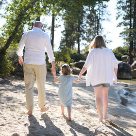 Mom and dad holding daughter's hand while walking in the sand at Lake Tahoe