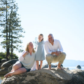 Mom and dad sit on a rock while daughter stands and smiles in Lake Tahoe