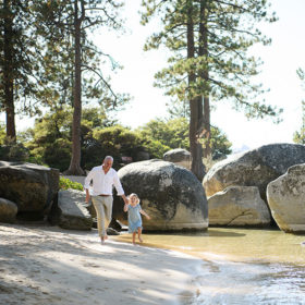 Dad and toddler daughter running on the beach at Lake Tahoe with rocks and trees in background