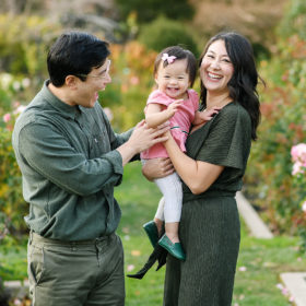 Mom and dad smiling and making toddler daughter laugh at McKinley Park Rose Garden Sacramento