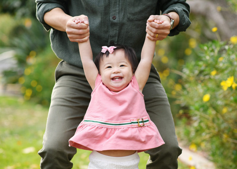 Dad holding toddler daughter by arms as she smiles at McKinley Park Sacramento